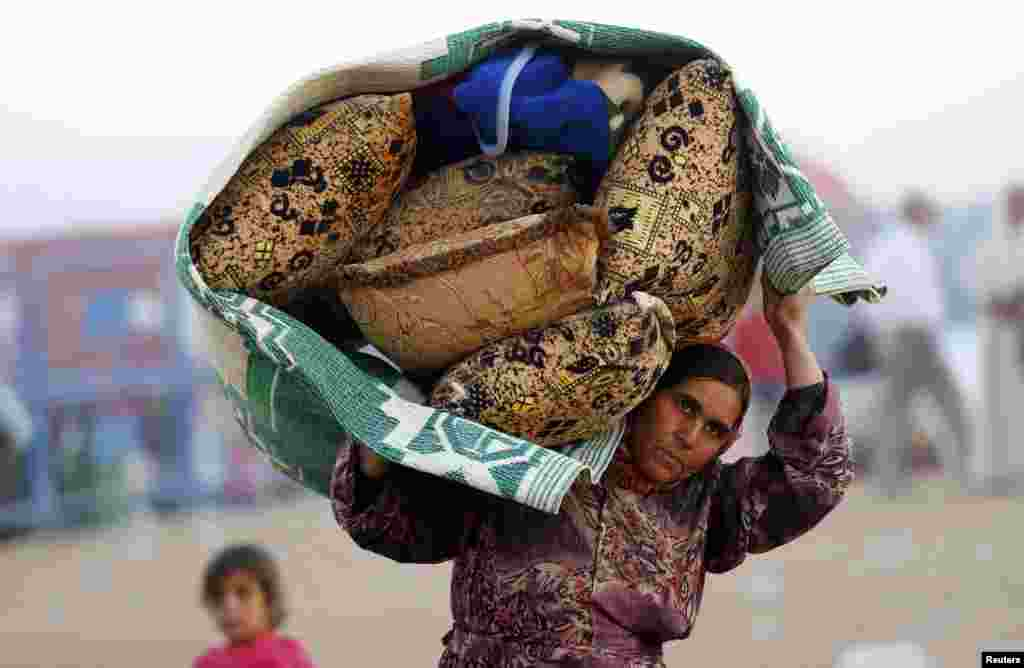 A Syrian Kurdish woman carries her belongings after crossing into Turkey near the southeastern town of Suruc in Sanliurfa province.