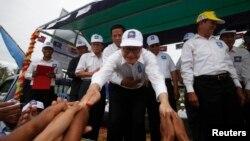 Pemimpin oposisi Kamboja, Sam Rainsy (tengah) menyalami para pendukungnya di provinsi Kampong Speu (20/7).