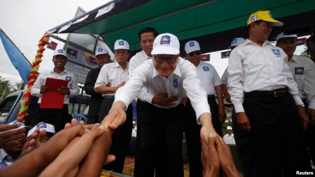 Cambodian opposition leader Sam Rainsy (C) greets his supporters in Kampong Speu province July 20, 2013.