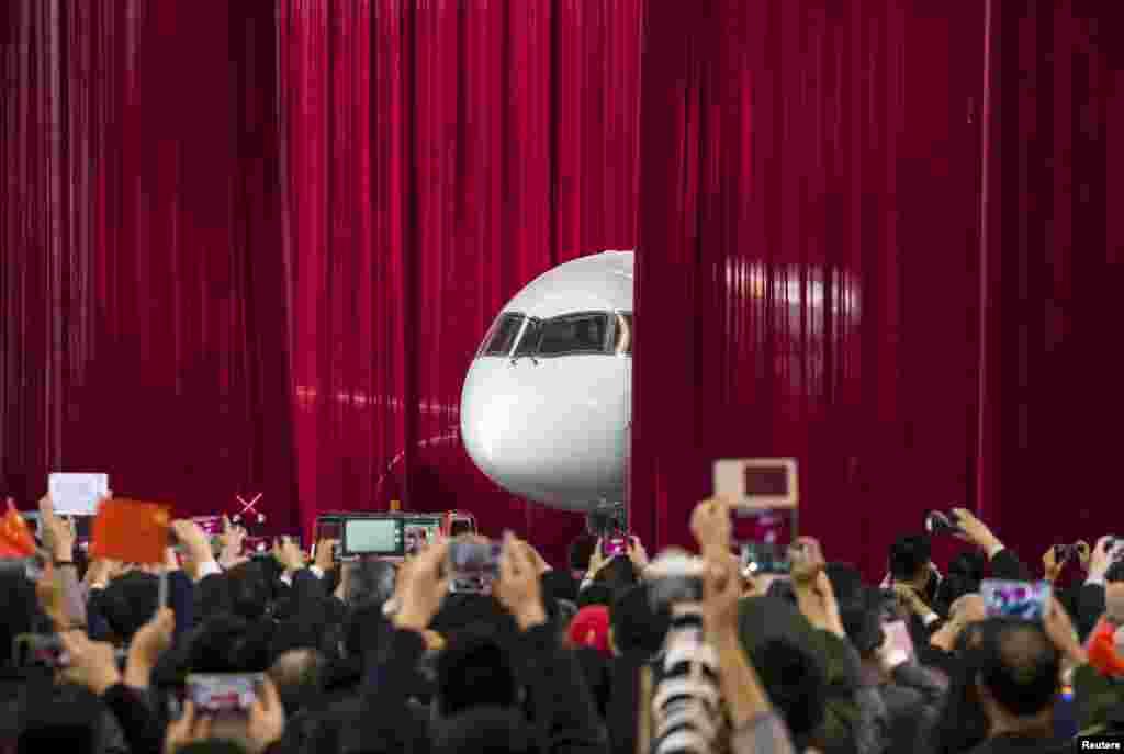 មនុស្សថតរូប និងថតវីដេអូ នៅពេលដែលយន្តហោះដឹកអ្នកដំណើរម៉ាក C919 ជាលើកដំបូងផលិតដោយក្រុមហ៊ុនCommercial Aircraft Corp of China (Comac) ត្រូវបានទាញចេញពីវាំងនន ក្នុងសន្និសីទកាសែតនៅរោងចក្ររបស់ក្រុមហ៊ុននៅក្នុងក្រុង Shanghai កាលពីថ្ងៃទី២ ខែវិច្ឆិកា ឆ្នាំ២០១៥។ ក្រុមហ៊ុន Comac បានបញ្ចេញយន្តហោះម៉ាក C919 ដែលមាន១៥៨កៅអីជាលើកដំបូង។ នេះការម៉ាកស្រដៀងទៅនឹងយន្តហោះរបស់ក្រុមហ៊ុន Airbus Group និងក្រុមហ៊ុន Boeing Co។