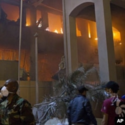 In this photo taken on a government organized tour, soldiers and civilians gather in front of a burning official building following an airstrike in Tripoli, Libya, May 17, 2011