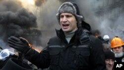 El líder opositor ucraniano Vitali Klitschko habla a manifestantes junto a barricadas en llamas en el centro de Kiev.