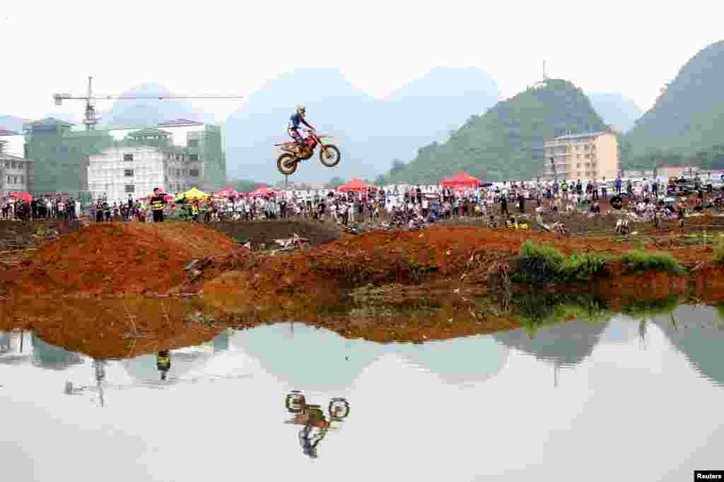 A rider rides a motorcycle in the air during a competition at Guilin, Guangxi Zhuang Autonomous Region, China.