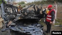 Pihak berwenang Pakistan di dekat sebuah mobil yang rusak setalah ditabrak oleh mobil pembom bunuh diri di Peshawar, Pakistan (3/9).