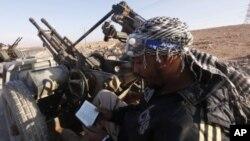 An anti-Gaddafi fighter reads the Koran at a checkpoint north of Bani Walid. (file photo)