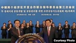 14일 베이징에서 경제 개발 협력에 합의한 후 악수하는 장성택 북한 국방위원회 부위원장(왼쪽)과 천더밍 중국 상무부장. 중국 상무부 웹사이트.