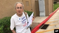 FILE - Rivko Knox, a volunteer with the League of Women Voters, collects signatures, April 19. 2018, for a campaign financing ballot measure outside a polling station in Glendale, Ariz. A judge, Aug. 24, 2018 upheld a 2016 Arizona law that bans groups from collecting early mail-in ballots from voters and delivering them.