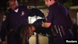 5月3日晚在巴尔的摩市,一名示威者无视宵禁规定被警察逮捕。