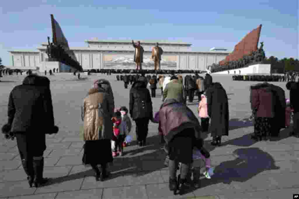 North Koreans bow before the statues of late leaders Kim Il Sung, left, and Kim Jong Il, right, at Mansu Hill in Pyongyang, North Korea, Monday, Dec. 17, 2012.