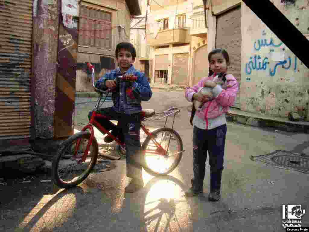 A Syrian boy and girl are seen posing for a photograph. Thirty minutes after the picture was taken a shell fired from a government-held position reportedly killed them both. Homs, January 20, 2013 (Lens Young Homsi)