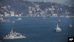 FILE - Turkish Navy vessels cross the Bosporus Strait in Istanbul, March 9, 2019, upon completion of massive military drills. A joint naval drill between Russia and Turkey last Friday in the Black Sea was part of Turkey's broader military exercise.