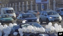 A car decorated of white balloons seen on the Moscow's Garden Ring road during a protest in Moscow, Russia, Sunday, Jan. 29, 2012. Hundreds of cars flying white ribbons or white balloons are driving around Moscow's Garden Ring in a show of support for a p