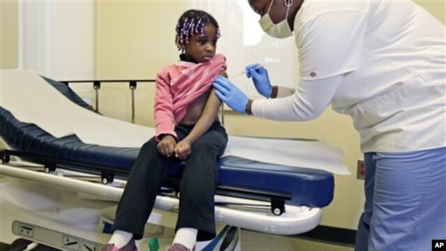 Four-year-old Gabriella Diaz sits as registered nurse Charlene Luxcin (R) administers a flu shot at the Whittier Street Health Center in Boston, Massachusetts, January 9, 2013. Boston declared a public health emergency and the state reported 18 flu-relate