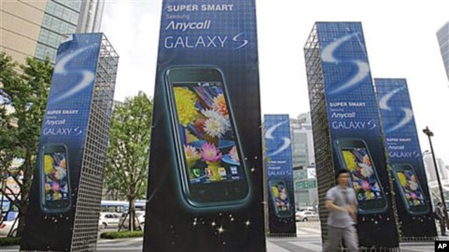 A man runs past Samsung Electronics Co.'s mobile phone Galaxy S advertisement outside its head office in Seoul, South Korea (FILE).