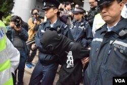 一名熱血公民成員(黑衣蒙頭者)涉嫌在法院外與親建制派人士發生踫撞,被警員帶走。(美國之音湯惠芸)