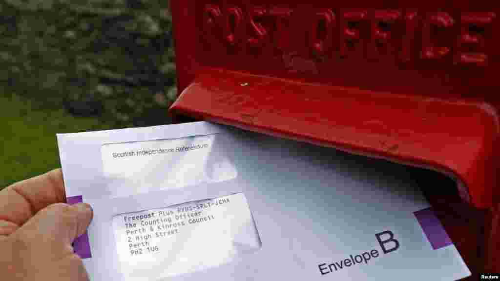 A postal vote for the Scottish Independence Referendum is dropped into a letter box in Moulin, Scotland, Sept. 12, 2014.