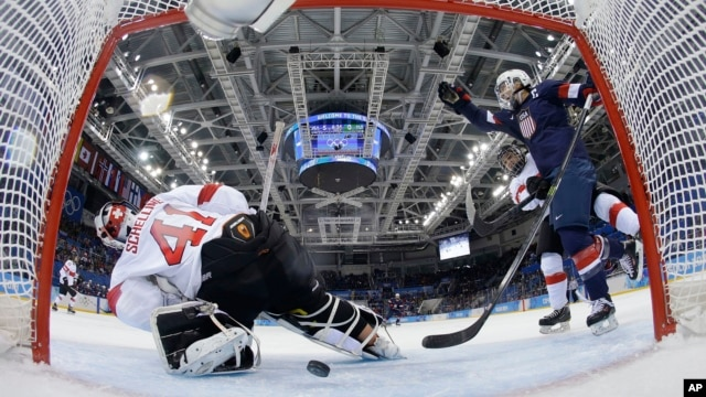 Meghan Duggan of the U.S. celebrates Monique Lamoureux's goal as the puck slides under Goalkeeper Florence Schelling of Switzerland during the second period of the 2014 Winter Olympics women's ice hockey game at Shayba Arena in Sochi, Russia, Feb. 10, 201