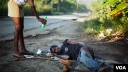 Una vecina ofrece agua a Antonio José, de 30años, tumbado en la carretera a las afueras de la capital.