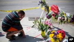 在南卡羅來納州教堂槍擊案出事地點附近的臨時追悼場所,有人哀悼(2015年6月18日)