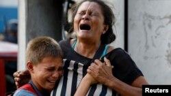 Parientes de uno de los reclusos lloran desesperados por tener noticias de los reos, 68 de los cuales murieron en un incendio en la Comandancia Central de Carabobo, el miércoles 28 de marzo.