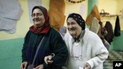 两名埃及妇女11月29日在开罗投票后正在离开投票站