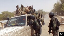 In this photo taken on Thursday, Feb. 19, 2015, Chadian soldiers on top of a truck, left, speak to Cameroon soldiers, right, standing next to the truck, on the border between Cameroon and Nigeria as they form part of the force to combat regional Islamic extremists force's including Boko Haram, near the town of Fotokol, Cameroon.
