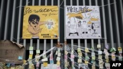 A placard showing a caricature of Kung Fu legend Bruce Lee (L) is displayed at the main protest site in the Admiralty district of Hong Kong, Oct. 23, 2014.