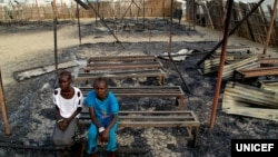 In this photo taken on 3 March 2016 in South Sudan, Chubat (right), 12, sits with her friend in the burned ruins of her school in Malakal Protection of Civilian site. (Hakim George/UNICEF)