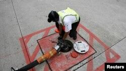 资料照:新加坡樟宜机场的一名技工将一条飞机加油管与停机坪下的储油罐出口连接起来。