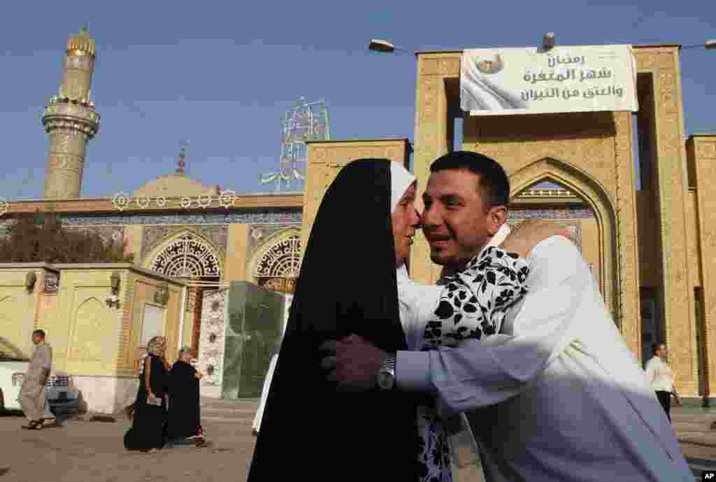 Iraqi Sunni Muslims exchange greetings after Eid prayers outside Abu Hanifa mosque at the first day of Eid al-Fitr prayers in the Azamiyah area of north Baghdad, Iraq, August 19, 2012.