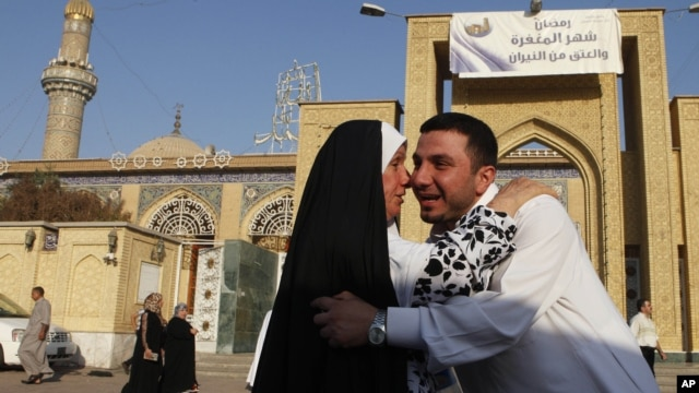 Iraqi Sunni Muslims exchange greetings after Eid prayers outside Abu Hanifa mosque at the first day of Eid al-Fitr prayers in Baghdad, Iraq, August 19, 2012.
