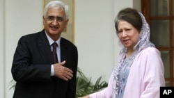 Indian Foreign Minister Salman Khurshid, left, prepares to shake hands with Bangladesh's opposition leader Khaleda Zia as they pose for the media before a meeting in New Delhi, India, October 30, 2012.