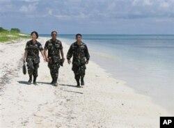菲律宾军人在卡拉扬群岛中的帕加萨岛(中国称中业岛)的沙滩上轻松散步(2008年5月资料照片)