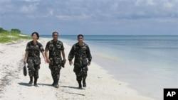 这张2008年5月的资料照片显示菲律宾军人在卡拉扬群岛中的帕加萨岛(中国称中业岛)的沙滩上轻松散步