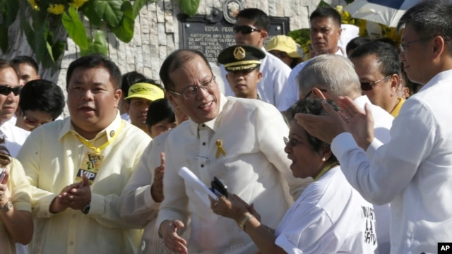 Philippine President Benigno Aquino III, center, is applauded by lawmakers after signing into law the Human Rights Victims Reparation and Recognition Act of 2013, Feb. 25, 2013.