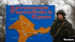 FILE - A Russian serviceman stands on duty near a map of the Crimea region near the city of Kerch, March 4, 2014.