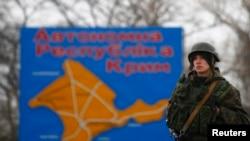 资料图片:俄罗斯士兵在接近刻赤市的一幅克里米亚地图前站岗。