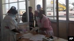 Des infirmières du ministère ougandais de la Santé passent au contrôle des passagers arrivant de la République démocratique du Congo, à l'aéroport d'Entebbe, à Kampala en Ouganda, le vendredi 8 août 2014.