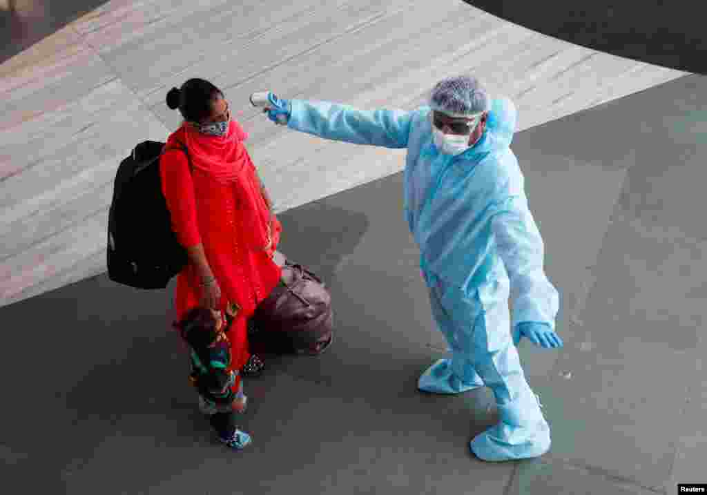 A health worker in personal protective equipment (PPE) checks the temperature of a passenger at a railway station, amid the spread of the coronavirus disease (COVID-19), in Mumbai, India November 27, 2020. REUTERS/Francis Mascarenhas TPX IMAGES OF THE