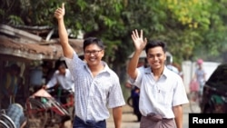 Reuters reporters Wa Lone and Kyaw Soe Oo gesture as they walk to Insein prison gate after being freed, after receiving a presidential pardon in Yangon, Myanmar, May 7, 2019.