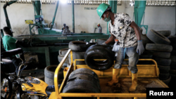 A worker offloads used car tires from a cargo tricycle in preparation for recycling at the Freetown waste management recycle factory in Ibadan, Nigeria September 17, 2021. (REUTERS/Temilade Adelaja)