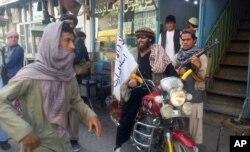 Chiến binh Taliban ngồi trên xe gắn cắm cờ Taliban trên đường phố ở thành phố Kunduz, ngày 29/9/2015.