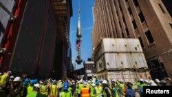 Giới truyền thông và công nhân chứng kiến đỉnh của Tòa nhà Trung tâm Thương mại được nâng lên để hoàn tất công đoạn cuối