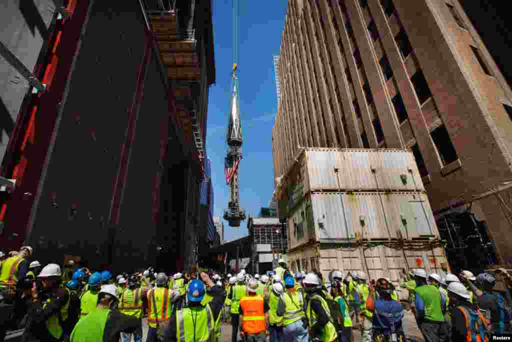 Members of the media and workers at the Ground Zero site watch as one of the last two segments of the silver spire is lifted to the top of One World Trade Center, May 2, 2013.