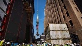 Para pekerja dan awak media di Ground Zero menyaksikan bagian yang akan menjadi puncak menara WTC dikerek untuk dipasang di puncak gedung itu di New York (2/5).