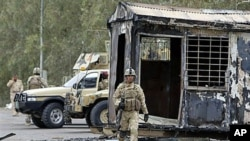 Iraqi army soldiers stand guard near burned trailers at Camp Ashraf, north of Baghdad, Iraq, April 2011 (file photo)