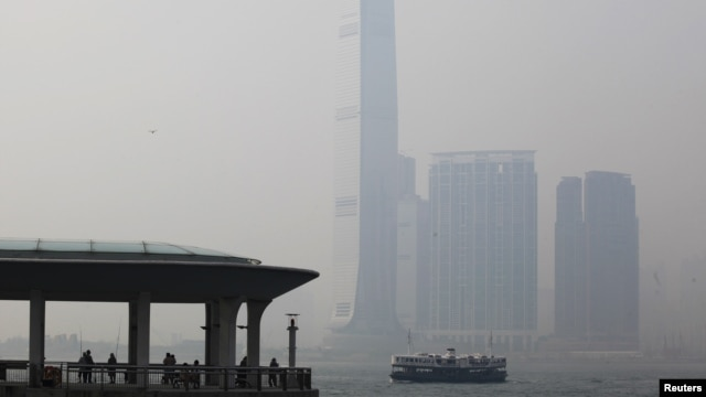 People rest at a ferry pier at the financial Central district under hazy weather in Hong Kong August 1, 2012. In the background, is the city's highest building, the International Commerce Centre in Kowloon peninsula.