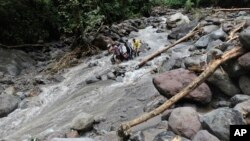 Rescuers carry the body of a victim after a flood hit Dua Warna waterfall in Sibolangit, North Sumatra, Indonesia, May 16, 2016.
