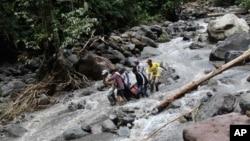 Regu penyelamat tengah membawa korban banjir yang melanda air terjun Dua Warna di Sibolangit, Sumatra Utara (16/5).
