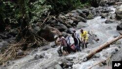 Para petugas mengangkat korban banjir bandang yang melanda air eerjun Dua Warna, Sibolangit, Sumatra Utara (Foto: dok).